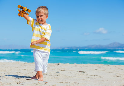 Child with toy plane at the beach